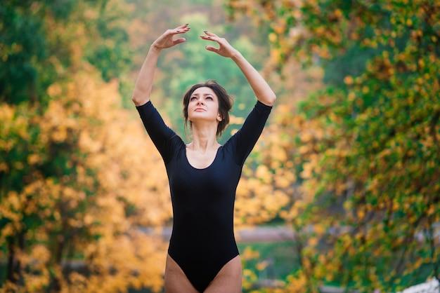 Mooie vrouw, ballerina, atleet in zwarte romper training in het park Premium Foto
