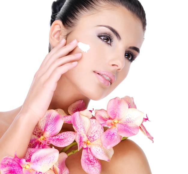 Mooie vrouw cosmetische crème toe te passen op gezicht met roze bloemen op lichaam - geïsoleerd op wit Gratis Foto