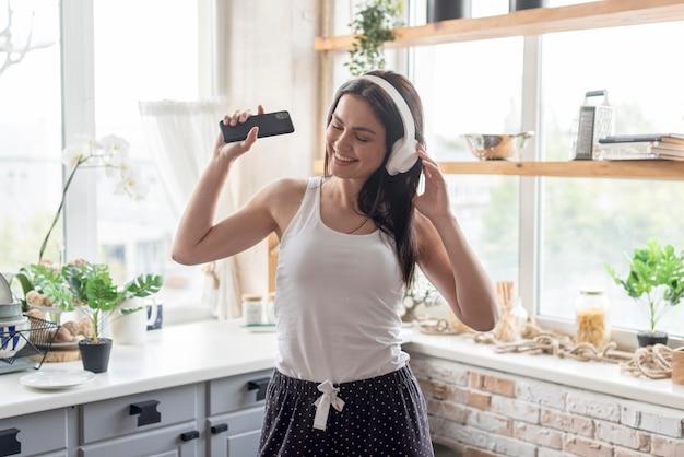 Mooie vrouw die aan muziek thuis luistert Gratis Foto