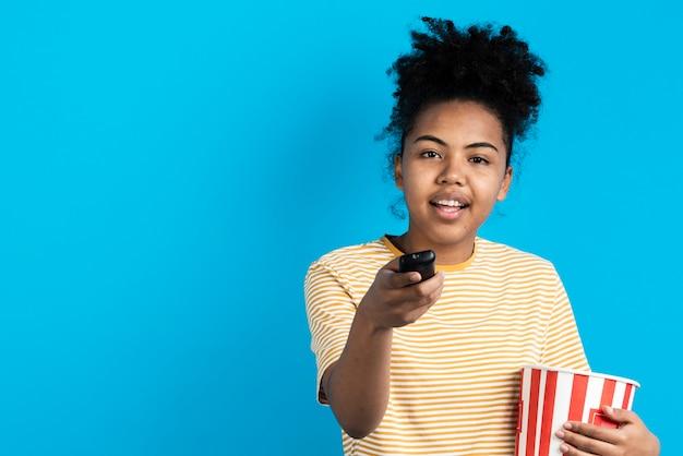 Mooie vrouw die afstandsbediening met popcornemmer richt Gratis Foto