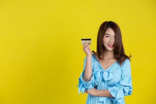 Mooie vrouw die bij camera glimlacht en creditcard op gele muur houdt Gratis Foto