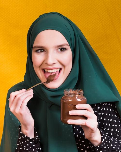 Mooie vrouw die de pot en de lepel van de chocoladeholding likken Gratis Foto