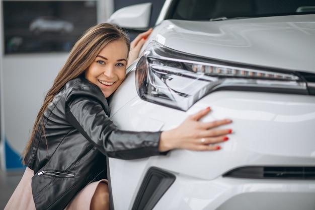 Mooie vrouw die een auto koestert Gratis Foto