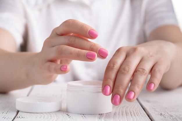 Mooie vrouw die een huidverzorgingsproduct, vochtinbrengende crème of lotion gebruikt die haar droge teint verzorgt. hydraterende crème in vrouwelijke handen Premium Foto