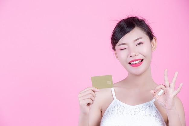 Mooie vrouw die een kaart op een roze achtergrond houdt. Gratis Foto