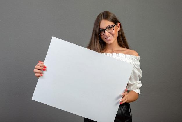 Mooie vrouw die een leeg aanplakbord houdt dat op grijze achtergrond wordt geïsoleerd Premium Foto