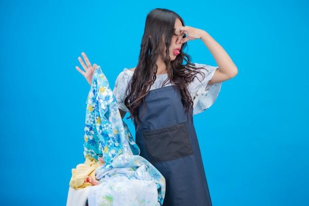 Mooie vrouw die een mand kleren op blauw houdt Gratis Foto