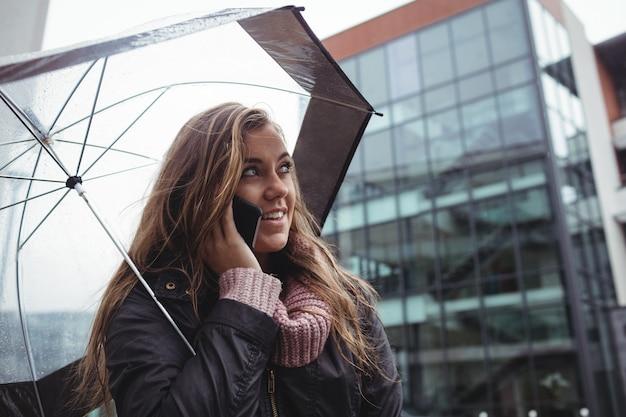 Mooie vrouw die een paraplu houdt en op mobiele telefoon spreekt Gratis Foto