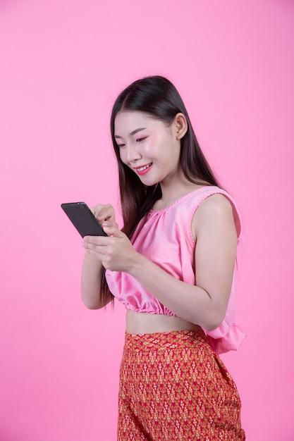 Mooie vrouw die een smartphone op een roze achtergrond houdt. Gratis Foto