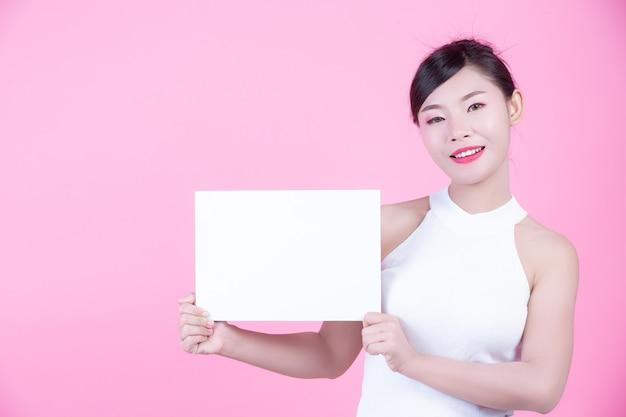 Mooie vrouw die een wit raadsblad op een roze achtergrond houdt. Gratis Foto