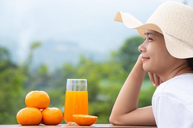 Mooie vrouw die een wit t-shirt met sinaasappelen draagt Gratis Foto