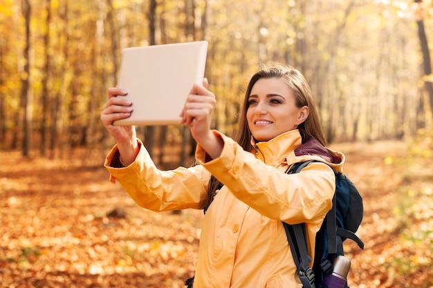 Mooie vrouw die foto neemt door digitale tablet Gratis Foto