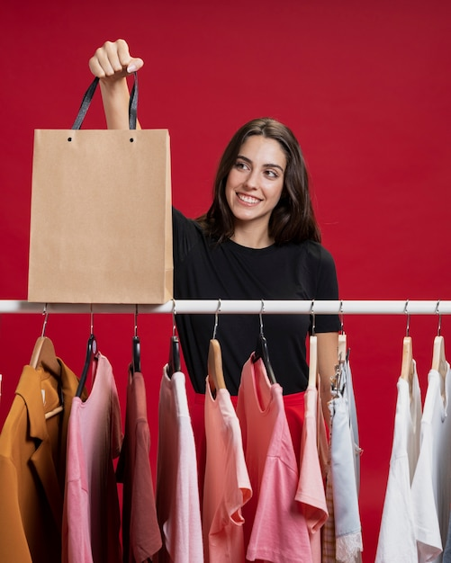 Mooie vrouw die haar het winkelen zak bekijkt Gratis Foto