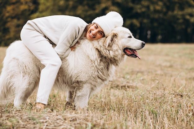 Mooie vrouw die haar hond op een gebied uitstapt Gratis Foto