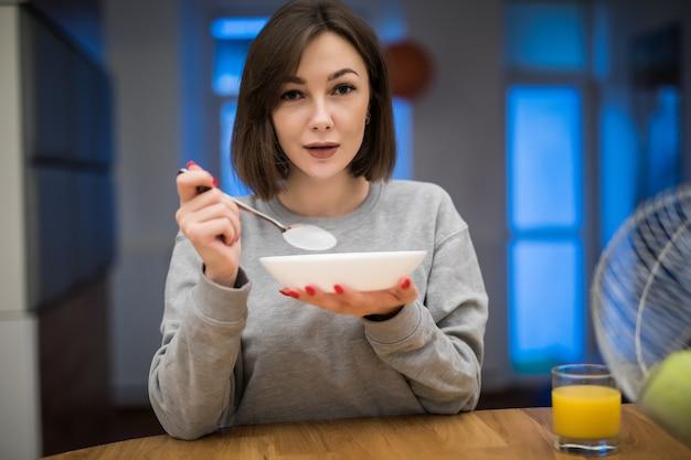 Mooie vrouw die haar ontbijtgranen in haar keuken eet Gratis Foto