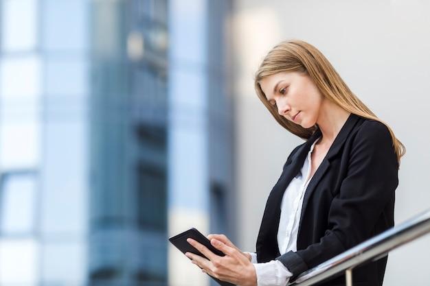 Mooie vrouw die haar tablet controleert Gratis Foto