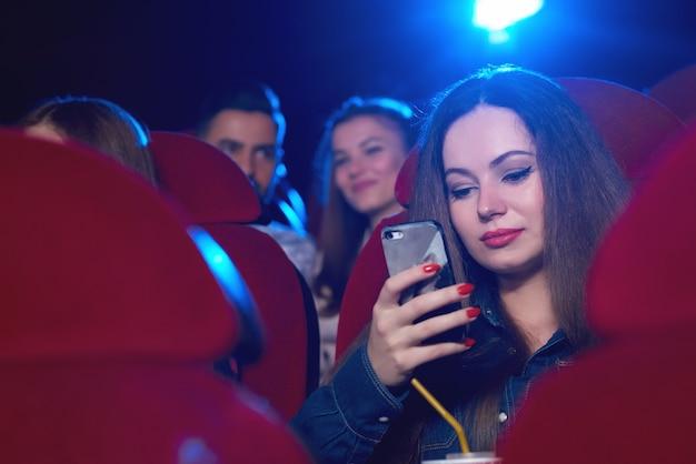 Mooie vrouw die haar telefoon met behulp van tijdens een saaie film bij de mededeling van de bioskoop copyspace technologie verveelde afleiding die online internet de verslaafde drager van de sociale gebruikersmobiliteit afleiden. Premium Foto