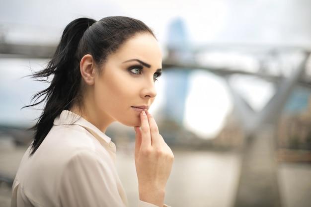 Mooie vrouw die het uitzicht bekijkt, dat over iets denkt Premium Foto