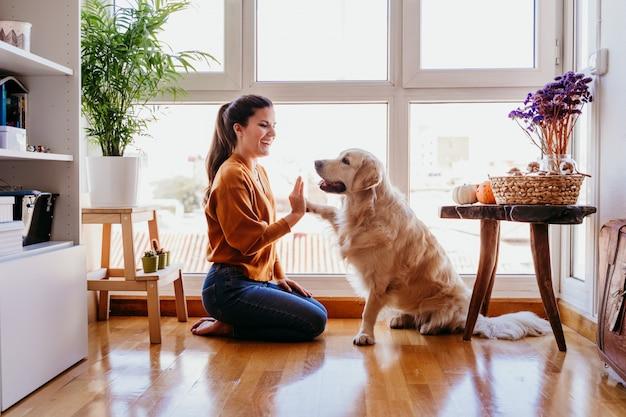 Mooie vrouw die hoogte vijf haar aanbiddelijke golden retrieverhond thuis doet. liefde voor dieren concept. levensstijl binnenshuis Premium Foto