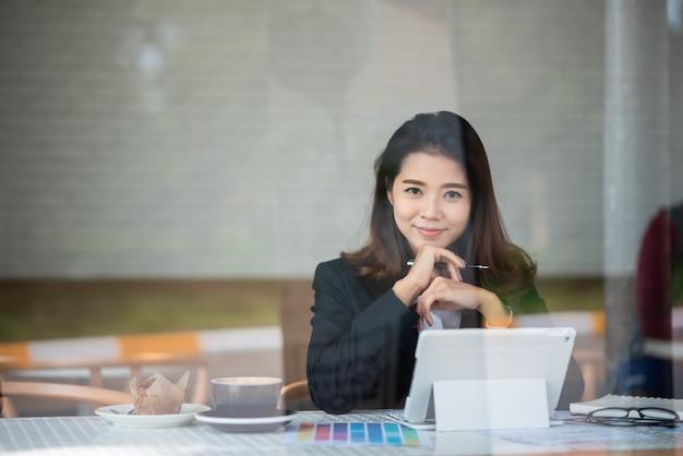 Mooie vrouw die in de koffie werkt Premium Foto