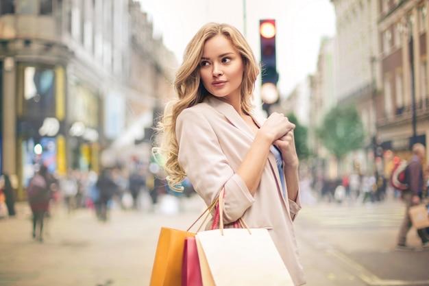 Mooie vrouw die in de straat loopt, die het winkelen zakken houdt Premium Foto