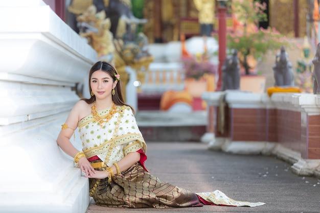 Mooie vrouw die in thaise traditionele uitrusting en zich bij tempel glimlacht bevindt Gratis Foto
