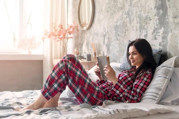 Mooie vrouw die lezingsboek in bed genieten van Premium Foto