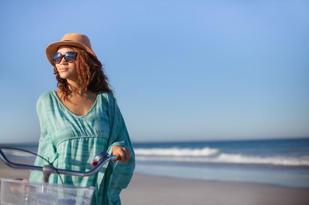 Mooie vrouw die met fiets op strand in de zonneschijn loopt Gratis Foto