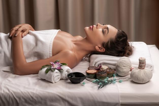 Mooie vrouw die met gelukkige stemming op vakantiedag ligt. wellness lichaamsverzorging en spa aromatheraphy concept. Premium Foto