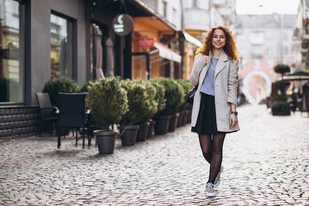 Mooie vrouw die met krullend haar bij een koffiestraat loopt Gratis Foto
