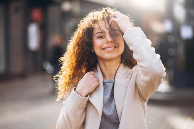 Mooie vrouw die met krullend haar in een de herfstlaag loopt Gratis Foto