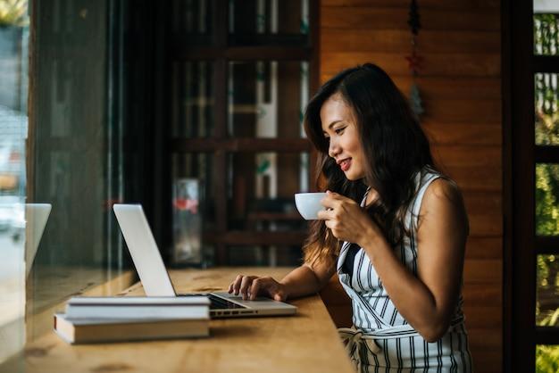 Mooie vrouw die met laptop computer bij koffiewinkelkoffie werkt Gratis Foto