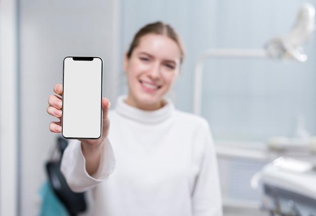 Mooie vrouw die mobiele telefoon houdt Gratis Foto