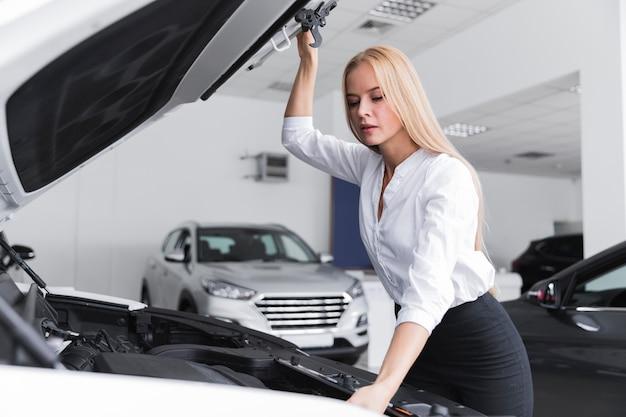 Mooie vrouw die onder motorkap van auto kijkt Gratis Foto