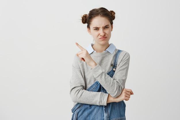 Mooie vrouw die ontevredenheid met het richten van vinger aan kant op iets vervelend uitdrukken. vrouwelijke ambtenaar die verstoord is van een nieuw schema dat erop gebaart, wat betekent dat ze genegeerd wordt. kopieer ruimte Gratis Foto