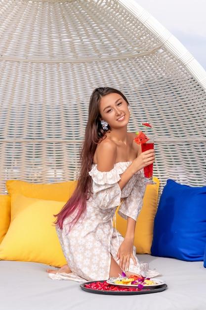 Mooie vrouw die op de strandbank rust en een cocktail drinkt Premium Foto