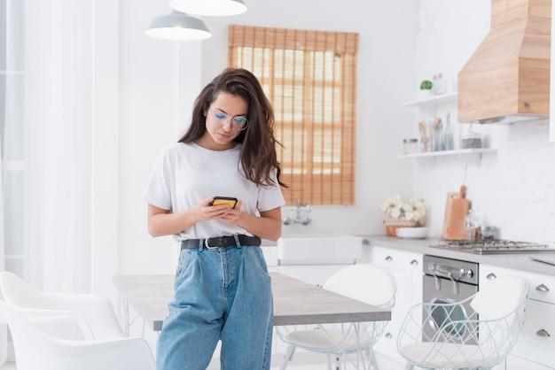 Mooie vrouw die op haar telefoon kijkt Gratis Foto