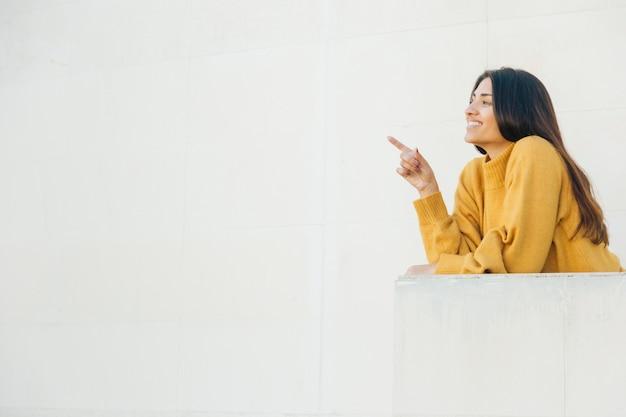 Mooie vrouw die op iets richt dat zich bij balkon bevindt Gratis Foto
