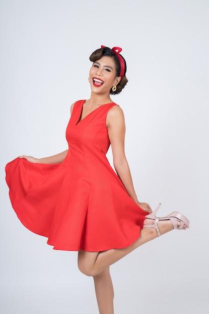 Mooie vrouw die rode kleding in studio draagt Gratis Foto