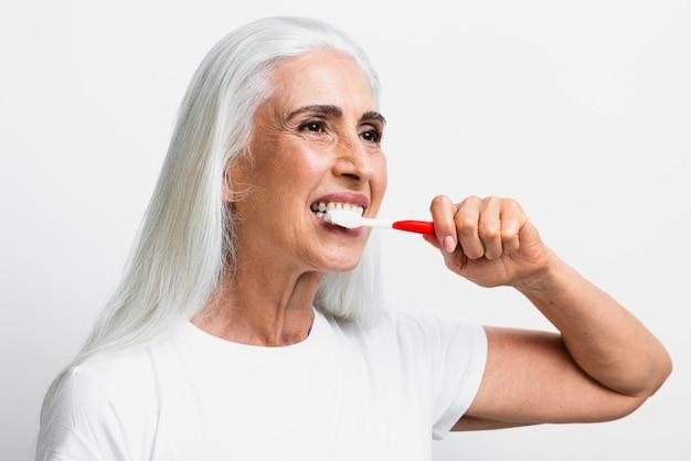 Mooie vrouw die tandenborstel gebruikt Gratis Foto