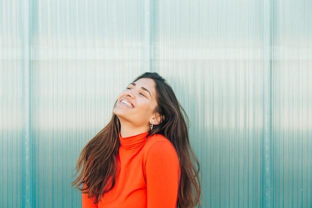 Mooie vrouw die tegen metaalachtergrond lacht Gratis Foto