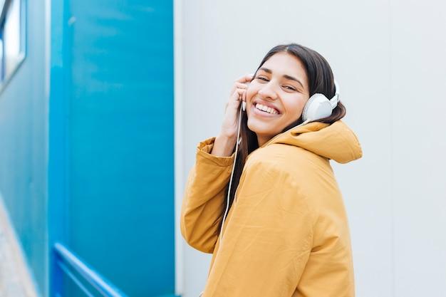 Mooie vrouw die terwijl het luisteren muziek lacht Gratis Foto