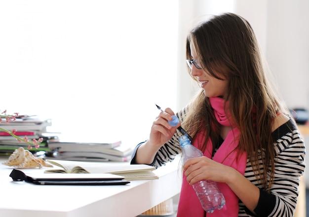 Mooie vrouw die thuis bestudeert Gratis Foto