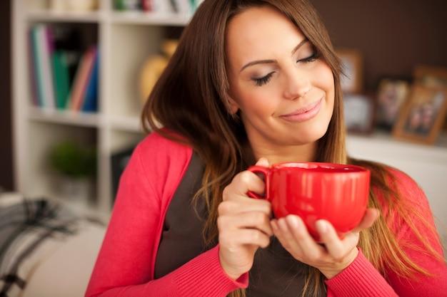 Mooie vrouw die van de geur van verse koffie geniet Gratis Foto