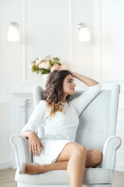 Mooie vrouw die witte kleding draagt en in witte leunstoel zit Gratis Foto