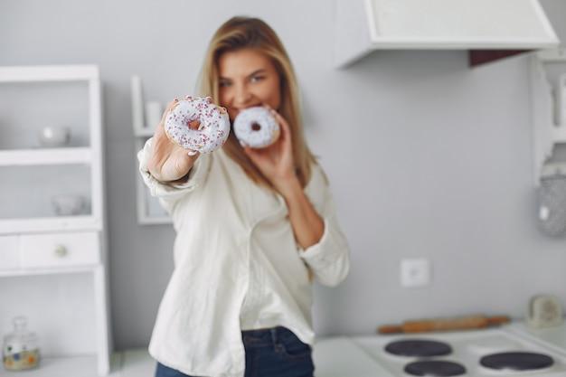 Mooie vrouw die zich in een keuken met doughnut bevindt Gratis Foto