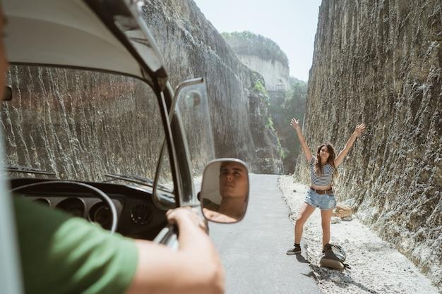 Mooie vrouw die zich op een weg bevindt met handen opheffen Premium Foto