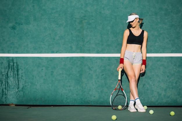 Mooie vrouw die zich voordeed op een tennisbaan Gratis Foto