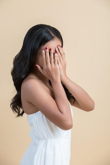 Mooie vrouw die zijn gezicht verbergt Gratis Foto