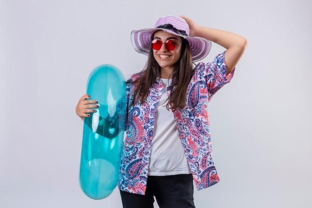 Mooie vrouw die zomerhoed en rode zonnebril draagt die opblaasbare ring positief houdt en gelukkig lachend vrolijk haar hoed staande te raken Gratis Foto